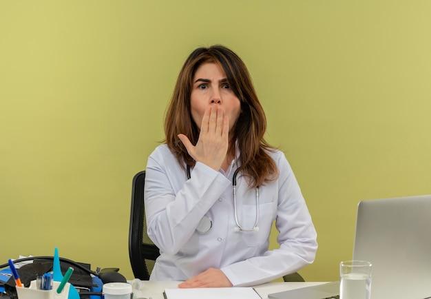 Médica de meia-idade surpresa, usando roupão médico e estetoscópio, sentada à mesa com a área de transferência de ferramentas médicas e laptop colocando a mão na boca