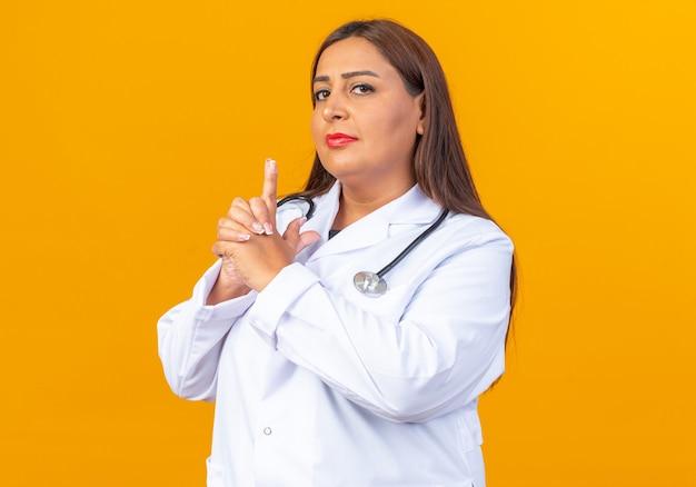 Médica de meia-idade usando jaleco branco com estetoscópio e rosto sério fazendo gesto de pistola com os dedos