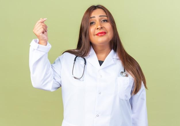 Médica de meia-idade usando jaleco branco com estetoscópio olhando para frente com um sorriso no rosto fazendo gesto de dinheiro esfregando os dedos em pé sobre a parede verde