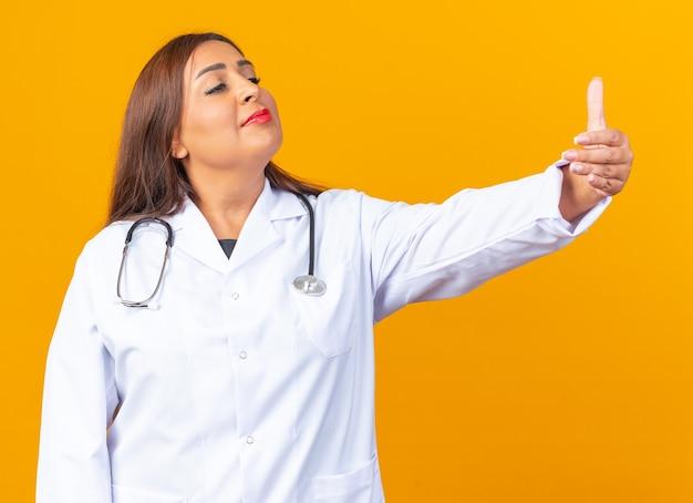 Médica de meia-idade usando jaleco branco com estetoscópio olhando para o lado com um sorriso confiante no rosto mostrando os polegares para cima