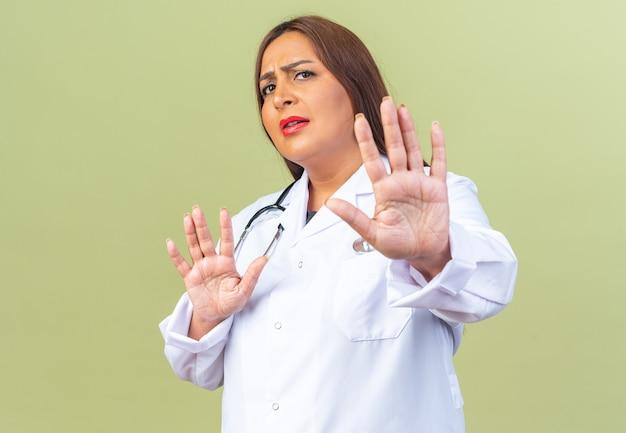 Médica de meia-idade usando jaleco branco com estetoscópio parecendo preocupada fazendo gesto de defesa com as mãos em pé no verde