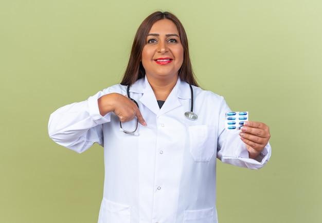 Médica de meia-idade usando jaleco branco com estetoscópio segurando uma bolha com comprimidos e um sorriso confiante apontando para ela mesma em pé no verde