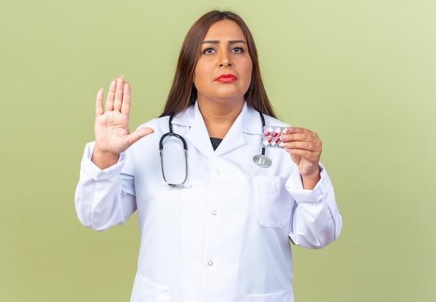 Médica de meia-idade usando jaleco branco com estetoscópio segurando uma bolha com comprimidos, olhando para a frente com uma cara séria, mostrando a mão aberta em pé sobre a parede verde