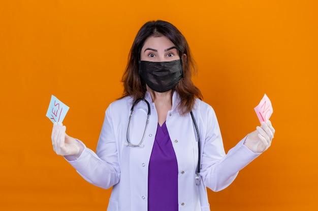 Médica de meia-idade usando jaleco branco com máscara facial protetora preta e com estetoscópio segurando papéis de lembrete com palavras de sim e não olhando para a câmera surpresa em pé sobre laranja