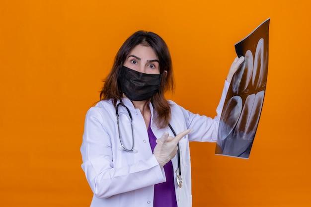 Médica de meia-idade usando jaleco branco com máscara facial protetora preta e estetoscópio segurando um raio-x dos pulmões parecendo surpresa apontando com o dedo indicador para o raio-x em pé sobre isola
