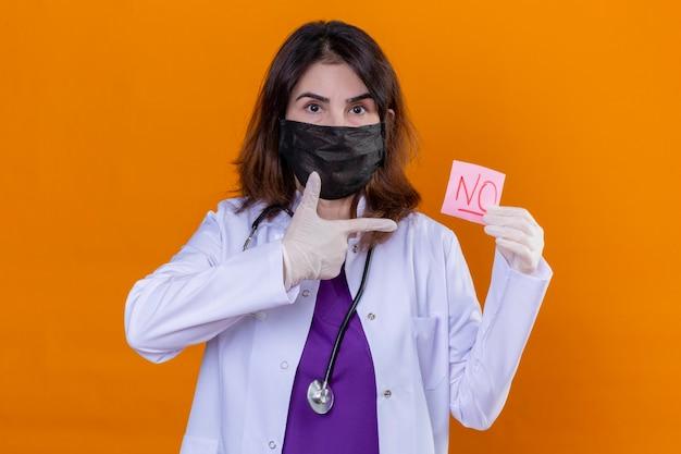 Médica de meia-idade usando jaleco branco em máscara facial protetora preta e com estetoscópio segurando um papel de lembrete sem nenhuma palavra apontando para ele sobre um fundo laranja isolado