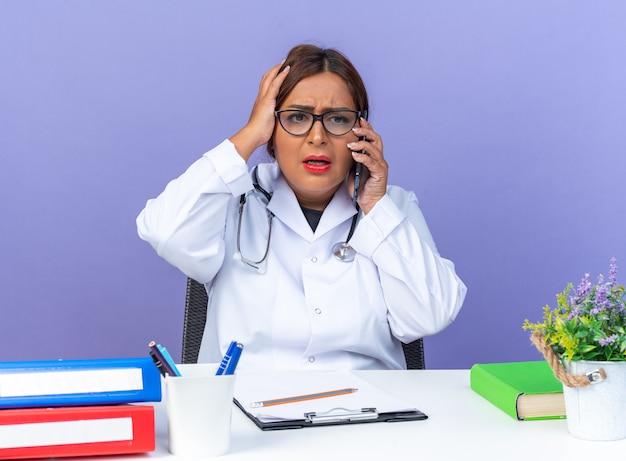 Médica de meia-idade vestindo jaleco branco com estetoscópio e óculos, parecendo confusa enquanto fala no celular, com a mão na cabeça por engano, sentada à mesa sobre a parede azul