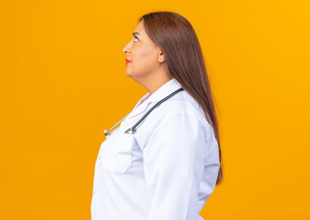 Médica de meia-idade vestindo jaleco branco com estetoscópio parecendo confiante em pé de lado na laranja