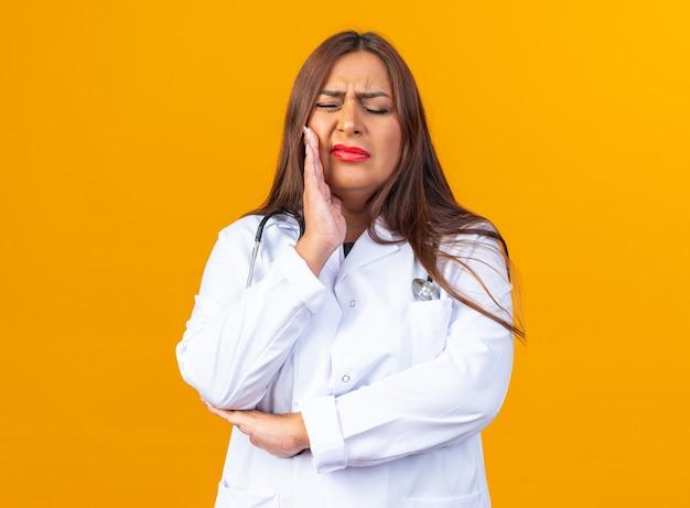 Médica de meia-idade vestindo jaleco branco com estetoscópio parecendo doente, tocando sua bochecha, sofrendo de dor de dente