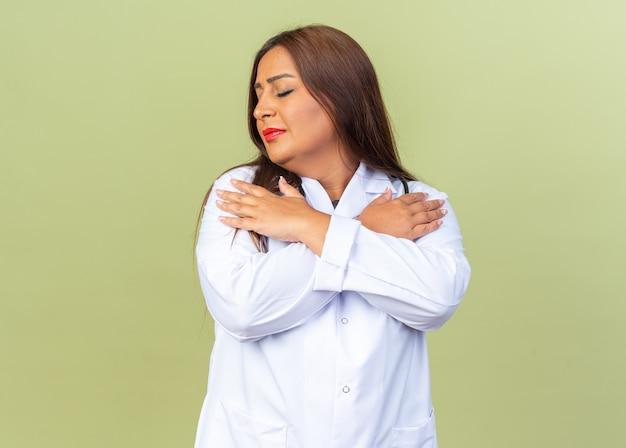 Médica de meia-idade vestindo jaleco branco com estetoscópio segurando as mãos no peito com os olhos fechados, sentindo emoções positivas em pé sobre uma parede verde