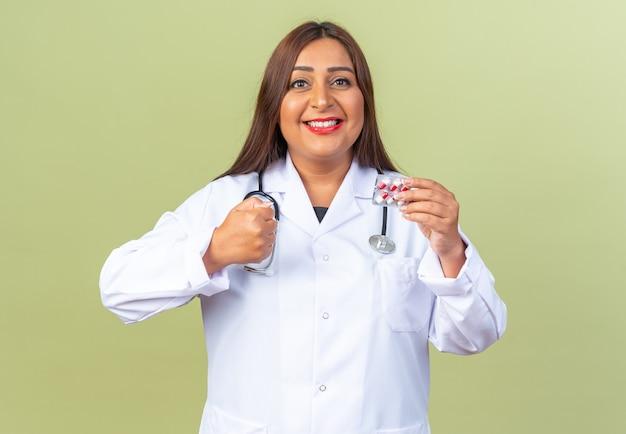 Médica de meia-idade vestindo jaleco branco com estetoscópio segurando uma bolha com comprimidos olhando para a frente feliz e animada com o punho cerrado em pé sobre a parede verde