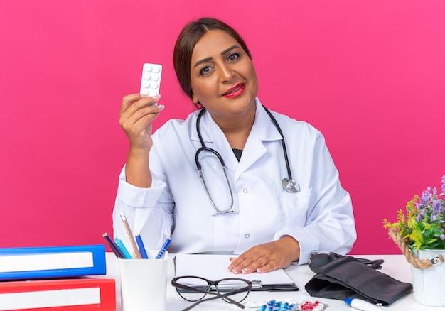 Médica de meia-idade vestindo jaleco branco com estetoscópio segurando uma bolha com comprimidos, olhando para a frente, sorrindo confiante, sentado à mesa com pastas de escritório sobre a parede rosa