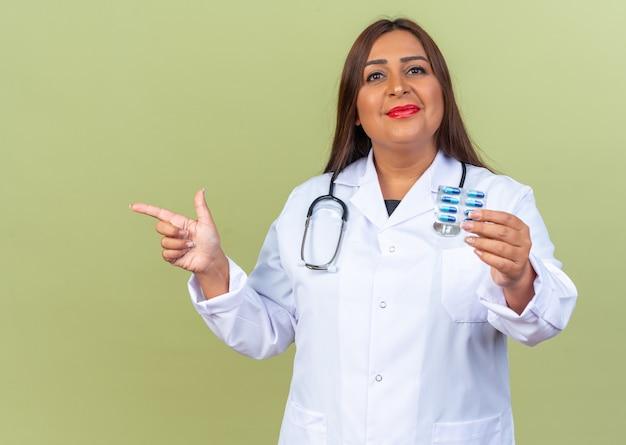 Médica de meia-idade vestindo jaleco branco com estetoscópio segurando uma bolha com comprimidos sorrindo alegremente apontando com o dedo indicador para o lado em pé no verde