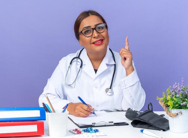 Médica de meia-idade vestindo jaleco branco com estetoscópio usando óculos, olhando para a frente, sorrindo confiante, mostrando o dedo indicador tendo uma nova ideia sentada à mesa sobre a parede azul