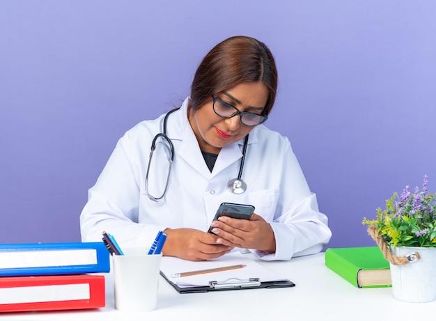 Médica de meia-idade vestindo jaleco branco com estetoscópio usando óculos segurando um smartphone olhando para ele com um sorriso no rosto, sentada à mesa sobre a parede azul