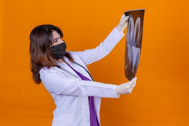 Médica de meia idade vestindo jaleco branco com máscara facial protetora preta e com estetoscópio segurando um raio-x dos pulmões, olhando com interesse para ele, de pé sobre um fundo laranja isolado