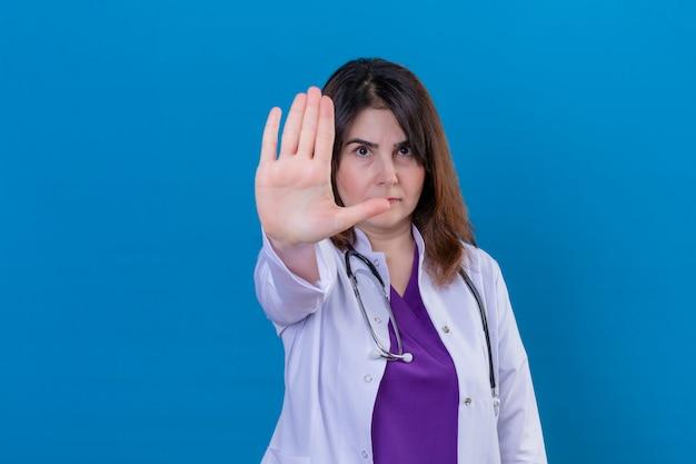 Médica de meia idade vestindo jaleco branco e com estetoscópio em pé com a mão aberta, fazendo sinal de pare com gesto de defesa de expressão sério e confiante sobre fundo azul