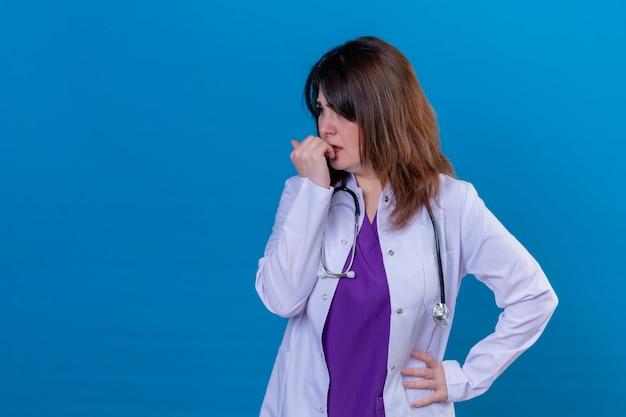 Médica de meia idade vestindo jaleco branco e com estetoscópio estressada e nervosa, roendo as unhas em pé sobre um fundo azul