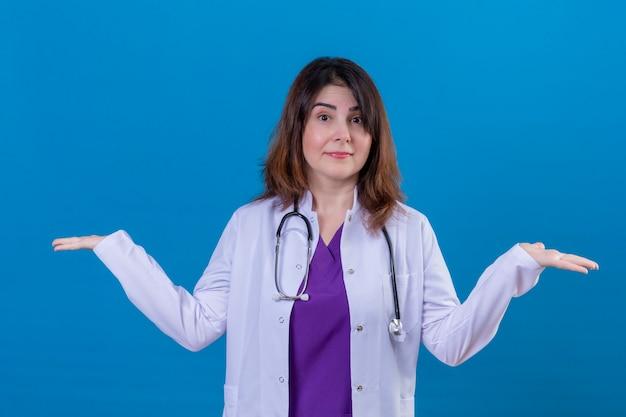 Médica de meia-idade vestindo jaleco branco e com estetoscópio sem noção e confusa com os braços abertos nenhuma ideia do conceito de pé sobre um fundo azul isolado