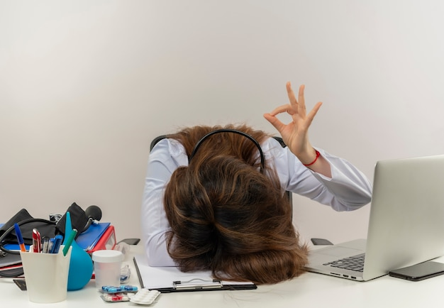 Médica de meia-idade vestindo túnica médica com estetoscópio sentada na mesa de trabalho no laptop com ferramentas médicas abaixou a cabeça e mostrando o gesto certo na parede branca com espaço de cópia