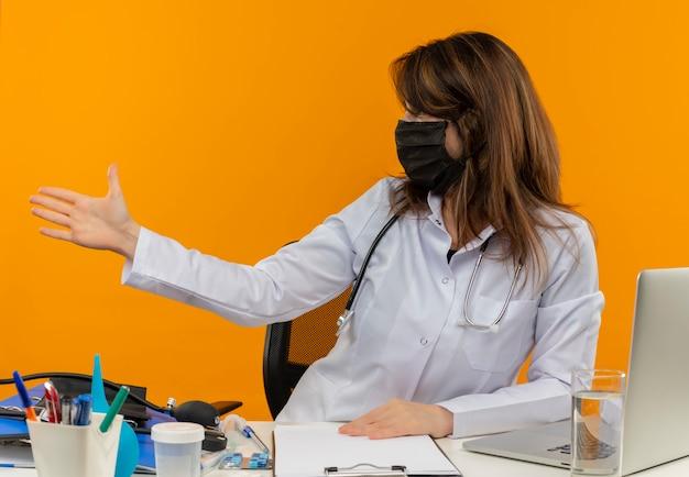 Médica de meia-idade vestindo túnica médica, estetoscópio e máscara, sentada na mesa com ferramentas médicas, laptop e prancheta, olhando e estendendo a mão para o lado isolado