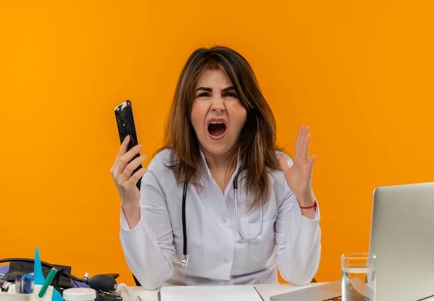 Médica de meia-idade zangada usando túnica médica e estetoscópio sentada na mesa com a área de transferência de ferramentas médicas e laptop segurando o telefone celular e mantendo a mão no ar