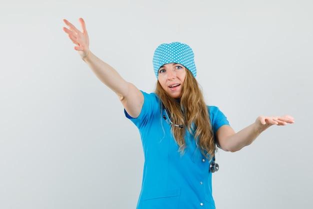 Médica de uniforme azul abrindo os braços para um abraço e parecendo alegre