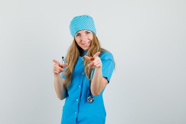 Médica de uniforme azul apontando para a câmera e parecendo feliz