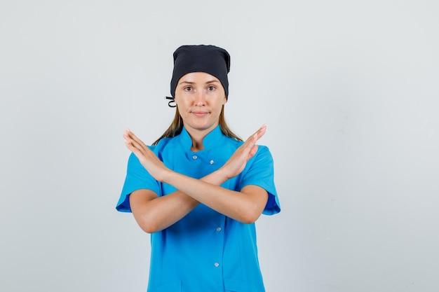 Médica de uniforme azul, chapéu preto e gesto de parar