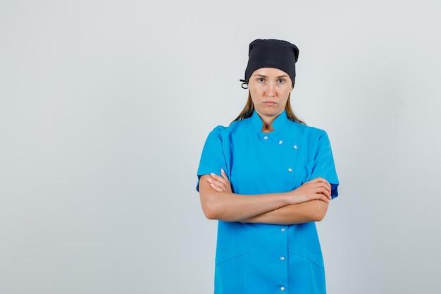 Médica de uniforme azul, chapéu preto em pé com os braços cruzados e aparência severa