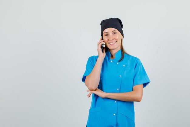 Médica de uniforme azul, chapéu preto, falando no smartphone e parecendo animada