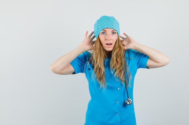Médica de uniforme azul com as mãos perto das orelhas e parecendo ansiosa