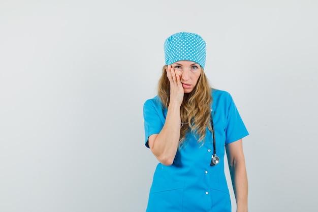 Médica de uniforme azul com dor de dente e parecendo doente