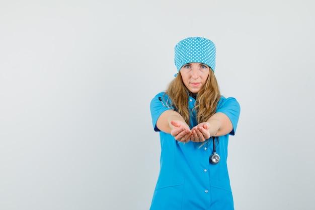 Médica de uniforme azul convidando para vir