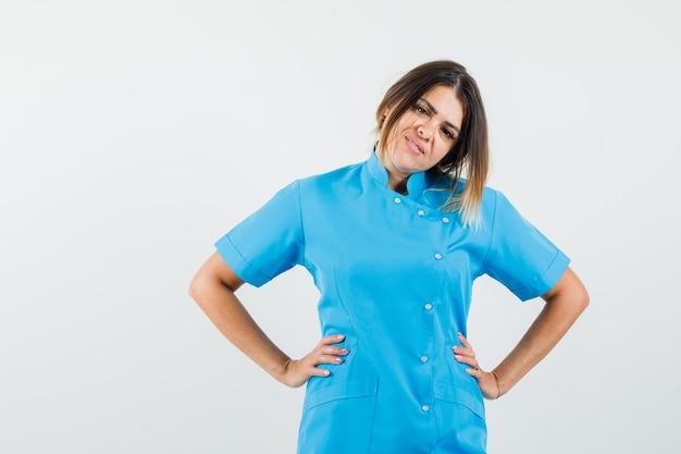 Médica de uniforme azul de mãos dadas na cintura e parecendo confiante