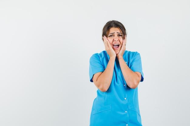 Médica de uniforme azul de mãos dadas no rosto e parecendo melancólica