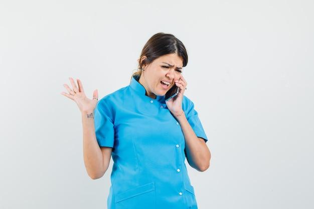 Médica de uniforme azul falando no celular e parecendo confusa