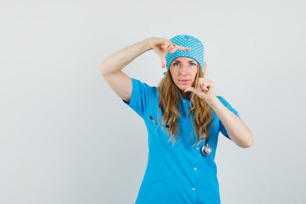 Médica de uniforme azul fazendo gesto de moldura