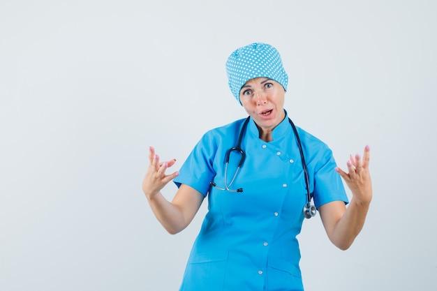 Médica de uniforme azul, levantando as mãos de maneira agressiva, vista frontal.