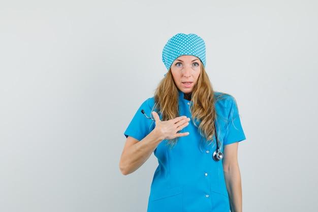 Médica de uniforme azul me fazendo gestos questionadores e parecendo confusa
