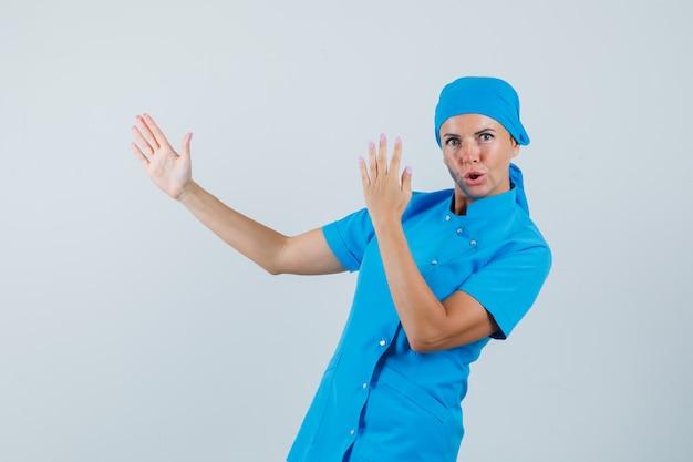 Médica de uniforme azul, mostrando o gesto de golpe de caratê e olhando confiante, vista frontal.