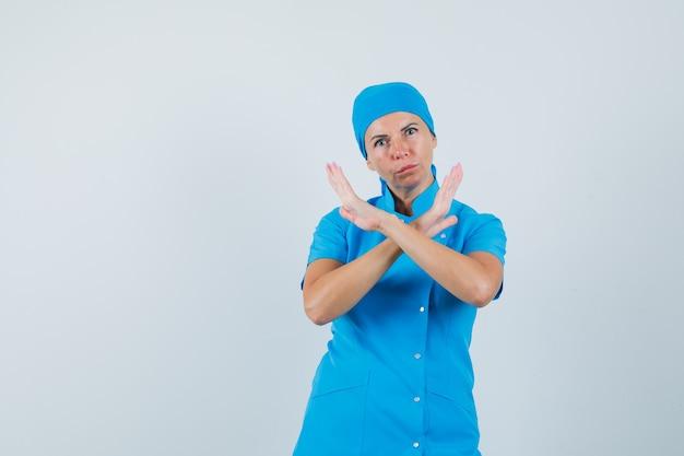 Médica de uniforme azul, mostrando o gesto de recusa e olhando séria, vista frontal.