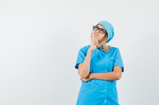 Médica de uniforme azul olhando para cima e parecendo pensativa