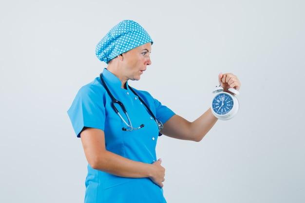 Médica de uniforme azul, olhando para o despertador e olhando animada, vista frontal.