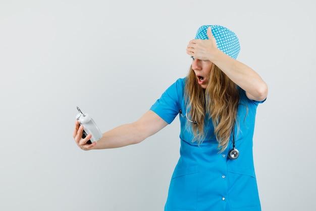 Médica de uniforme azul olhando para o despertador e parecendo agitada