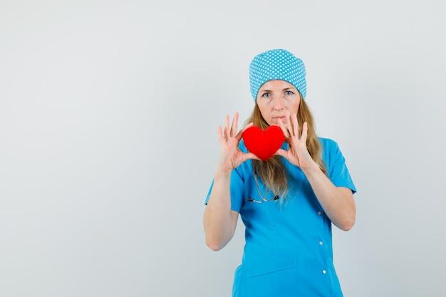 Médica de uniforme azul segurando um coração vermelho