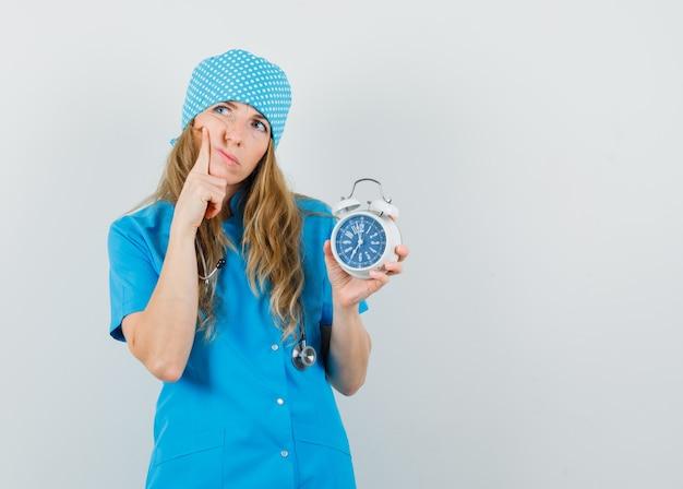 Médica de uniforme azul segurando um despertador e olhando pensativa