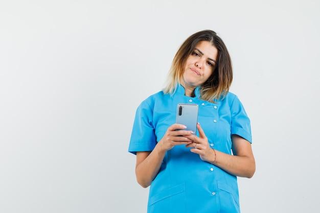 Médica de uniforme azul segurando um telefone celular e parecendo pensativa