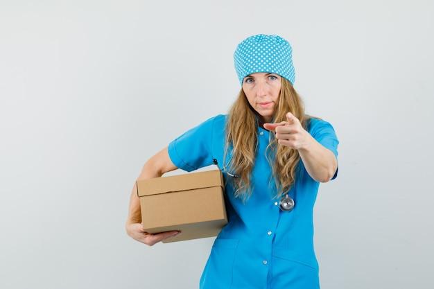 Médica de uniforme azul segurando uma caixa de papelão e apontando para a câmera