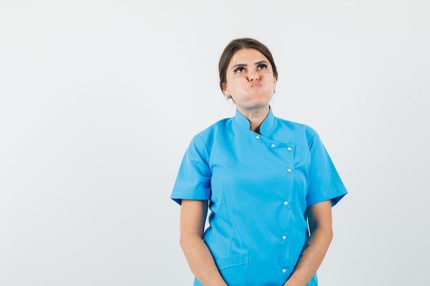 Médica de uniforme azul soprando nas bochechas e parecendo melancólica